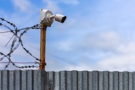 Profiled sheet fence with cheap surveillance camera and barbwire with selective focus.