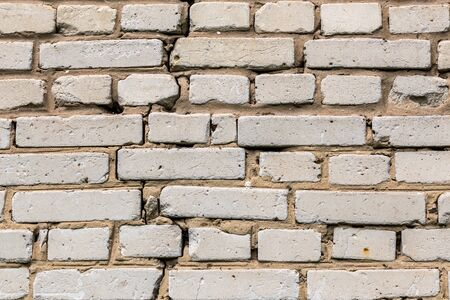 Deep cracked white silicate brick wall closeup texture and background. Horizontal shot.