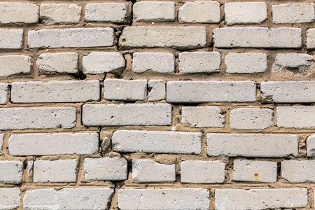 Deep cracked white silicate brick wall closeup texture and background. Horizontal shot.