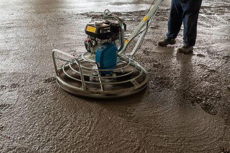 Power-Float-Schleifmaschine auf nassem Betonhintergrund Nahaufnahme mit selektivem Fokus und Boke-Unschärfe erschossen