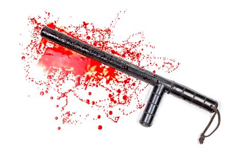 Bloody russian police rubber tonfa baton in blood spatter isolated on white background in top-down flat lay perspective.