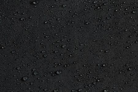 Primer plano de tela plana hidrofóbica impermeable gris oscuro con fondo de gotas de lluvia Foto de archivo
