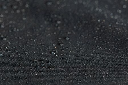 dark gray waterproof hydrophobic flat cloth closeup with rain drops selective focus background Фото со стока
