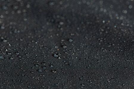 primo piano in tessuto piatto idrofobo impermeabile grigio scuro con gocce di pioggia messa a fuoco selettiva sfondo