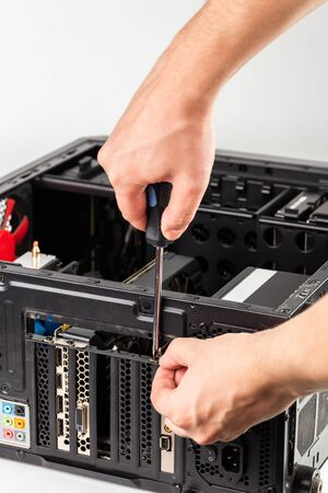 hands unscrewing a video card bracket while maintenance personal computer hardware with selective focus