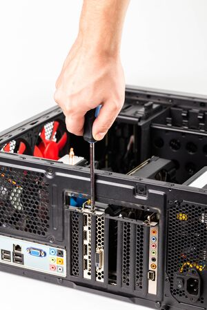 right caucasian hand unscrewing a video card bracket while maintenance personal computer hardware with selective focus Stock fotó