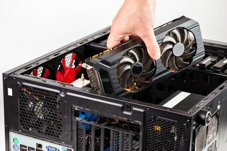 collegare a mano una scheda video durante la manutenzione dell'hardware del personal computer con messa a fuoco selettiva Archivio Fotografico