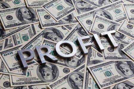 The word PROFIT laid with aluminium letters on the US dollar banknotes background - with selective focus Stock fotó