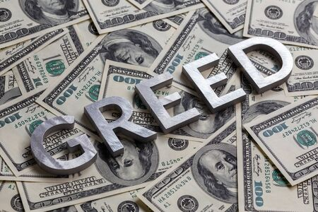 The word GREED laid with aluminium letters on the US dollar banknotes background - with selective focus
