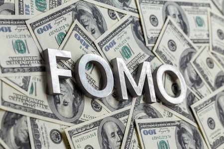 The word FOMO laid with aluminium letters on the US dollar banknotes background - with selective focus