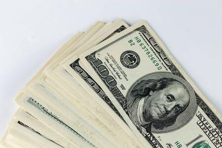 a skewed stack of old us dollar banknotes on white background - close shot
