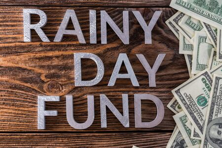 words RAINY DAY FUND laid on wooden surface by metal letters with rain drops and us dollar banknotes Imagens
