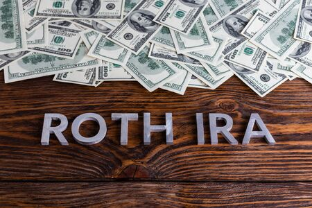 words ROTH IRA laid on wooden surface by metal letters with us dollar banknotes 免版税图像