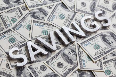 Het woord BESPARINGEN gelegd met witte metalen letters op de achtergrond van de Amerikaanse dollarbankbiljetten met selectieve focus