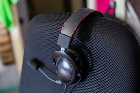 black headset on backrest of empty computer chair with air mesh upholstery