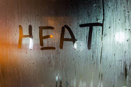 das Wort Hitze geschrieben auf nachtnassem Fensterglas Nahaufnahme mit Bokeh-Hintergrund