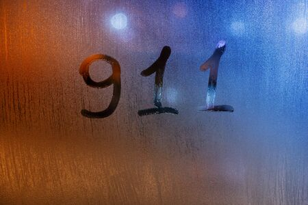 the word 911 written by finger on wet glass with blurred lights in background 版權商用圖片