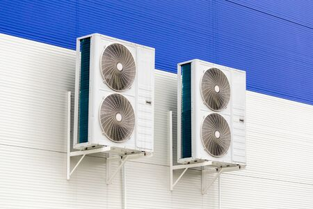 two double condensing units of air conditioner on blue and white metal industrial wall. Stock Photo