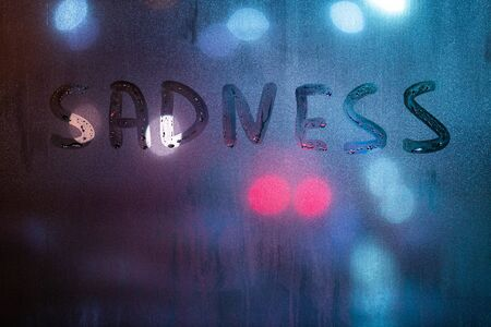 the word sadness written by finger on night wet glass with blurred blue and red lights in background.