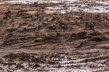 dirty mud road background at winter with selective focus and blur