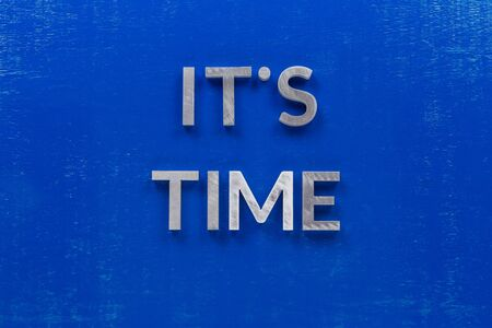 The phrase its time laid on blue painted board with thick silver metal aphabet characters., centered composition concept