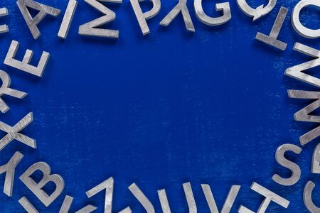 Frame mockup made of of silver metal english alphabet characters on blue background. Usable for back to school or language education projects. 版權商用圖片