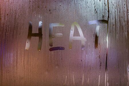 La palabra calor escrito en la noche de cristal de la ventana húmeda de cerca con fondo bokeh