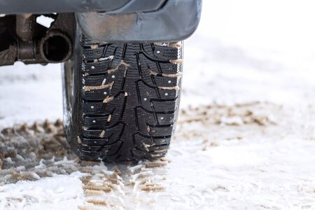 an unadorned picture of winter car wheel with metal spikes on snow close-up Stock fotó