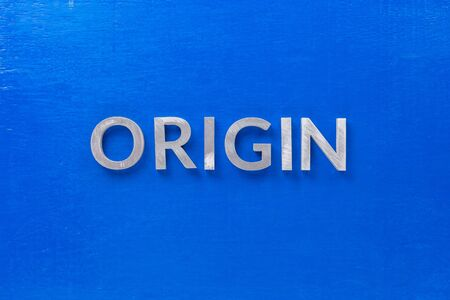 the word origin laid with silver metal characters on blue board in flat lay centered composition