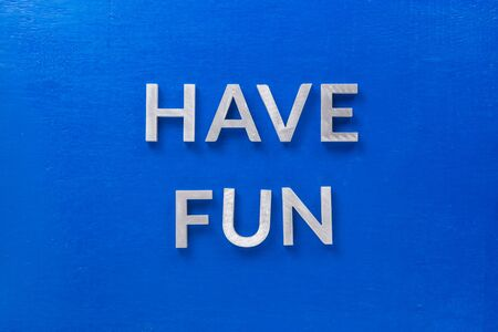 the words have fun laid with silver metal characters on blue painted wooden board in central flat lay composition