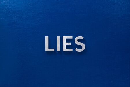 the word lie laid with silver metal letters on classic blue board in flat lay with central composition.