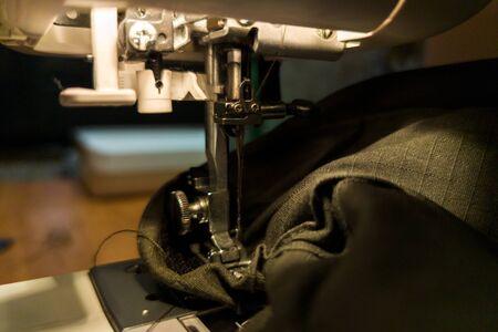 a dark gomestic sewing with machine and green military cloth Archivio Fotografico