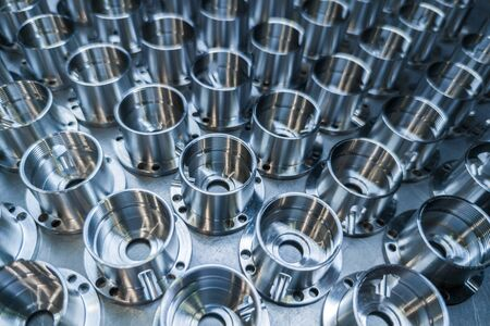 a batch of shiny metal cnc aerospace parts production - close-up with selective focus for industrial background. Imagens