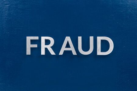 the word fraud laid with silver metal letters on classic blue painted board surface