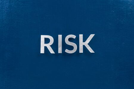 the words risk laid with silver metal letters on classic blue surface for stock market background