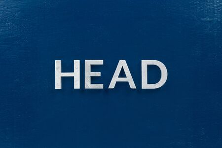 the word head laid with silver metal letters on classic blue painted board background Banco de Imagens
