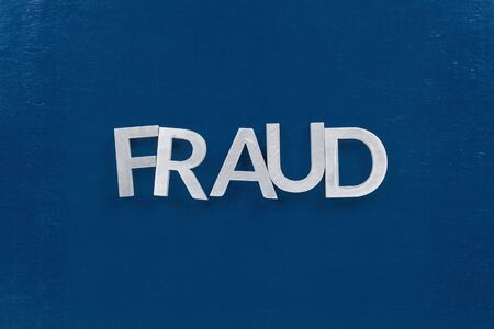the word fraud laid with silver metal letters on classic blue painted board surface - wtih careless dodging order