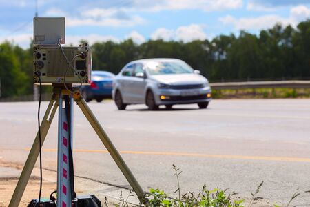 mobile speed camera device working on summer daytime road with blurry white car in background - view from back