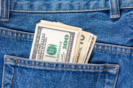 US dollar banknotes in the left rearpocket of blue jeans. Concept of saving money or pocket expenses.