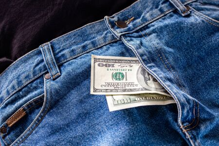 a two hundred dollar bills inside codpiece of blue jeans close-up with selective focus