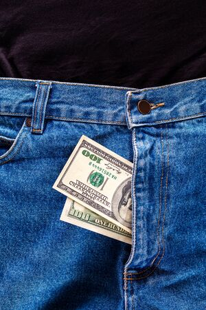 a two hundred dollar bills inside a fly of blue jeans close-up with selective focus