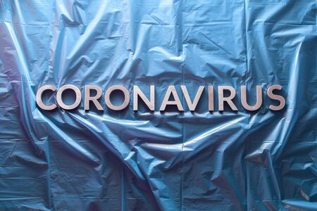 the word coronavirus laid with silver letters on crumpled blue plastic film - flat lay with centered composition