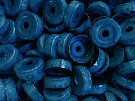 a pile of dirty black stamped metal round shells after a hood operation - - classic blue color toned
