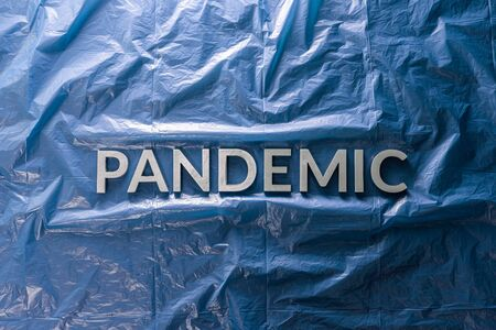 the word pandemic laid with silver letters on crumpled blue plastic film background in flat lay composition at center