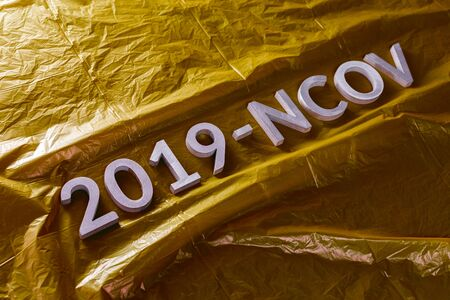 The word 2019-NCOV laid with metal letters on yellow crumpled plastic film background in slanted diagonal composition