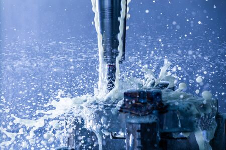Abstract process of vertical cnc steel milling in slim hydraulic clamping chuck with external water coolant streams and splashes, close-up with blue tone, selective focus and background blur. Fast shutter speed for motion freezing.