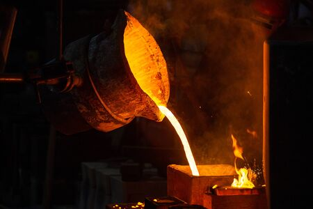 Close-up view of industrial chill casting with selective focus. The process of for filling out mold with molten metal. Archivio Fotografico