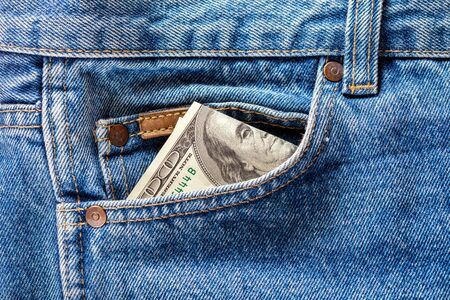 a hundred dollar banknote sticking out from front pocket of jeans - close-up 版權商用圖片