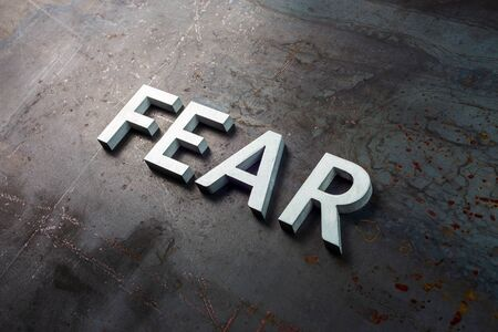 the word fear laid with silver letters on raw rusted steel sheet surface in slanted diagonal composition