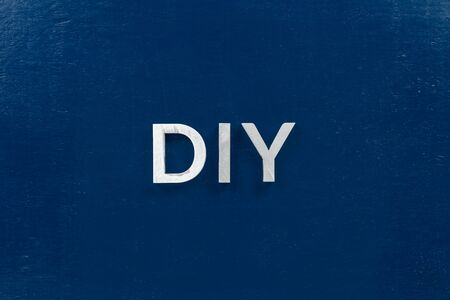 the abbreviation diy - do it yourself - laid with aluminium letters over dark blue flat surface, directly above perspective